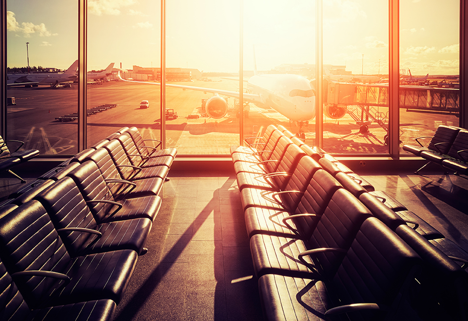 Empty seats in an airport departure hall at sunset, color toned picture, travel and transportation concept.
